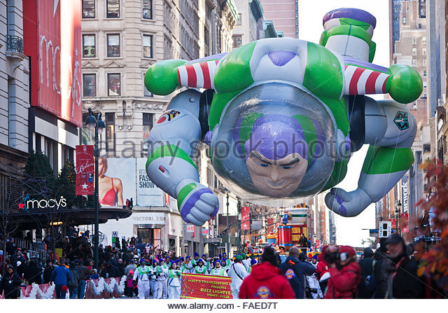 Buzz Lightyear cartoon character balloon floats past crowds during the annual Macy's Thanksgiving Day parade - Stock Image