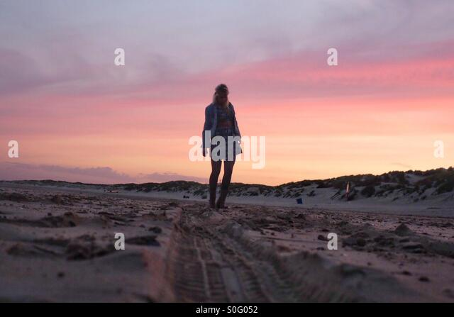 Young girl walking on a beach in the sunset - Stock Image