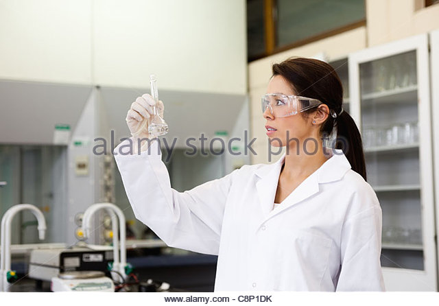 Chemist looking at a Erlenmeyer flask - Stock Image