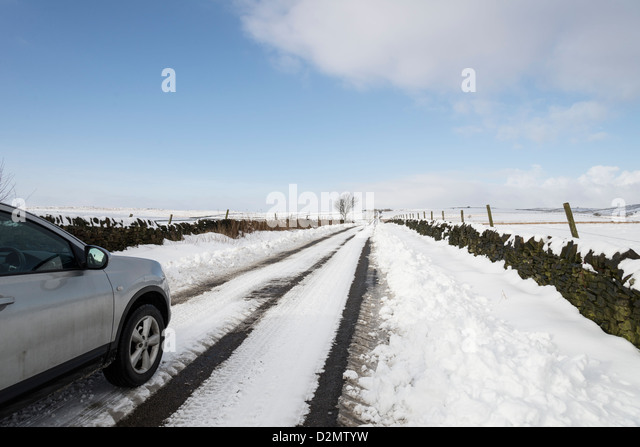 Stationary Silver car  on long narrow road covered in snow in  the Peak District Derbyshire England - Stock Image