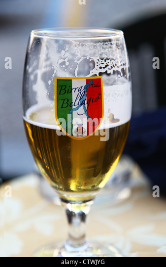 A glass half full or half empty of Birra Bellagio or beer from Bellagio Lake Como Italy Italian lakes - Stock Image