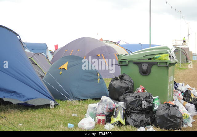 Rubbish overflows from a large bin by festival goers' tents on the final day of  the Y Not festival, Peak District - Stock Image