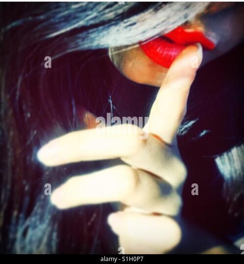 Close up of a young woman holding her finger to her red lips - Stock-Bilder
