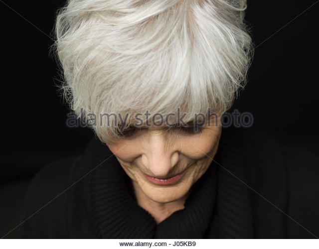 Close up portrait senior woman with short white hair looking down against black background - Stock Image