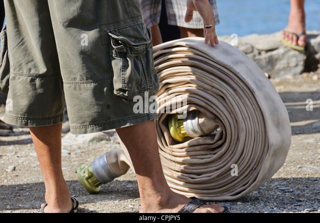 Man rolls Fire Hose Roll Firefighting Equipment Fire Drill, Sabang, Puerto Galera, Oriental Mindoro, Philippines, - Stock Image