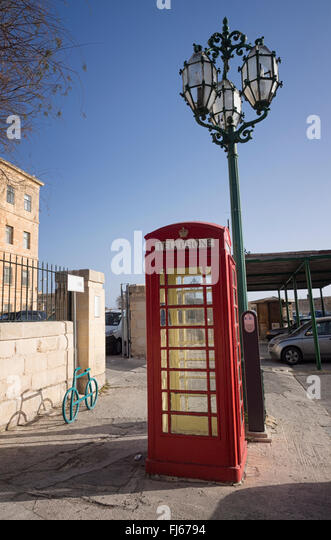 British-style red telephone box on a street in Valletta, capital of the island state of Malta in the Mediterranean - Stock Image