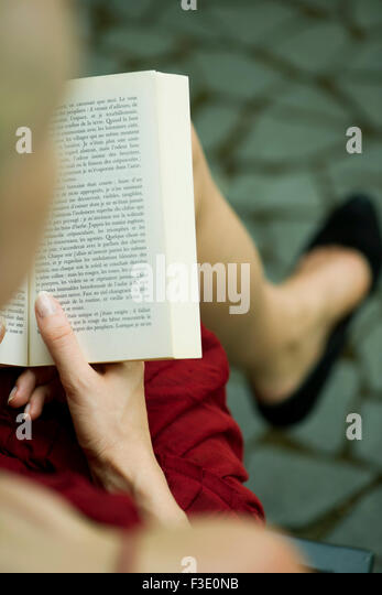 Woman reading book, over the shoulder view - Stock Image
