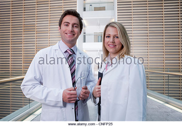 Portrait of smiling doctors wearing lab coats in hospital corridor - Stock Image