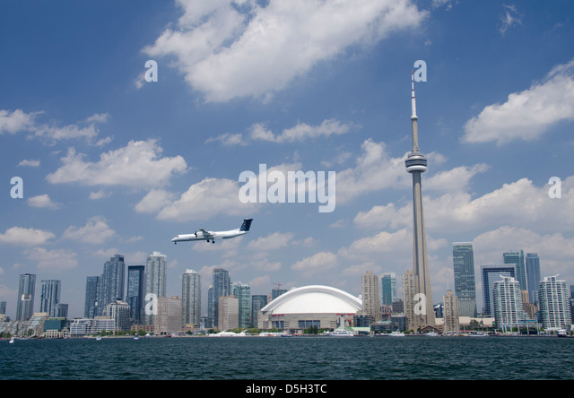Canada, Ontario, Toronto. Lake Ontario city skyline view of the iconic CN Tower and the Rogers Centre. Porter airplane. - Stock Image