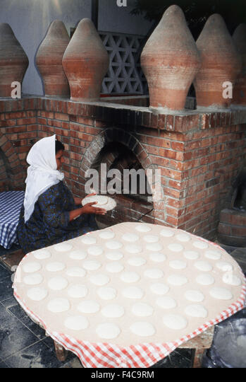 Egypt, Cairo, Women baking traditional bread in outside oven - Stock-Bilder
