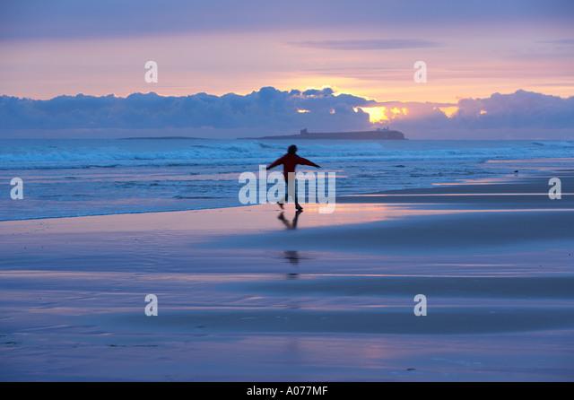 joyful solitary woman on the beach at dawn Bamburgh Castle Northumbria England UK - Stock Image
