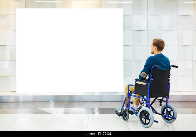 Disable guy in wheelchair looking at blank poster on the wall - Stock Image