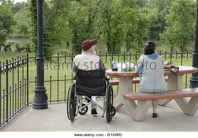 Arkansas Pocahontas Black River Overlook Park man woman couple wheelchair amputee picnic bench disabled handicapped - Stock Image