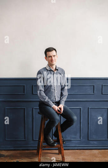 Portrait of Middle Eastern man sitting on stool - Stock-Bilder