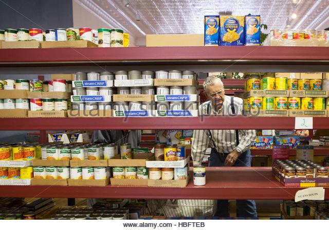 A man chooses food at the Jordan River Food Pantry. - Stock Image