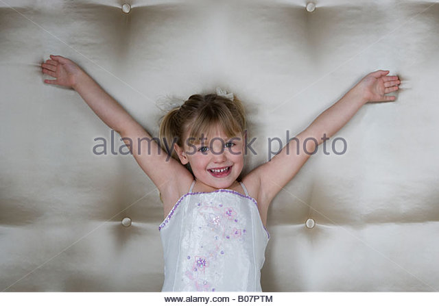 Little girl in a party dress with arms outstretched - Stock Image