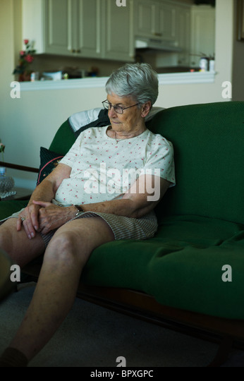 Sad-looking woman sitting on living couch with hands clasped in her lap. - Stock Image