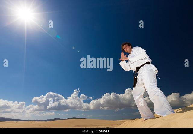Black belt martial artist training on desert dunes. - Stock-Bilder