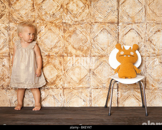 Little girl scared of stuffed animal on chair - Stock-Bilder