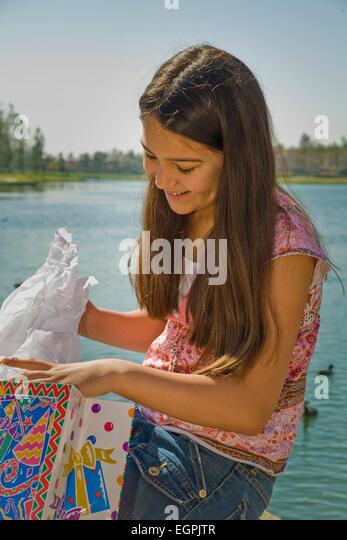 Mexican heritage. Hispanic/Caucasian girl 11-13 year old opens opening  birthday present gift.  MR  © Myrleen - Stock-Bilder