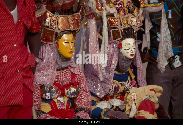 SIERRA LEONE West Africa Masked Kaka Devil secret society initiate dancers sitting on ground - Stock Image