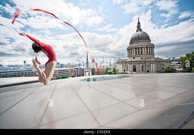 Dancer with ribbon on urban rooftop - Stock Image