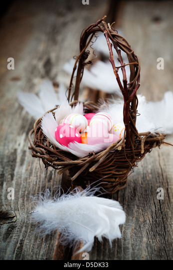 Colorful easter eggs in basket with white feathers - Stock Image