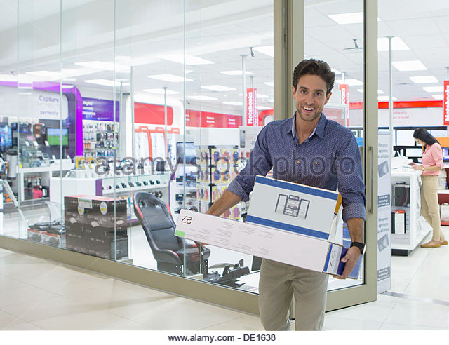 Portrait of smiling man leaving electronics store with boxes - Stock-Bilder