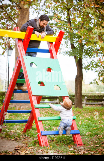 Father and son playing together on jungle gym, Osijek, Croatia - Stock-Bilder