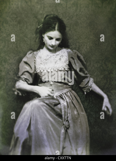 A woman sitting by a decorative wallpaper, with dark hair and closed eyes, dressed in a historical baroque / victorian - Stock-Bilder