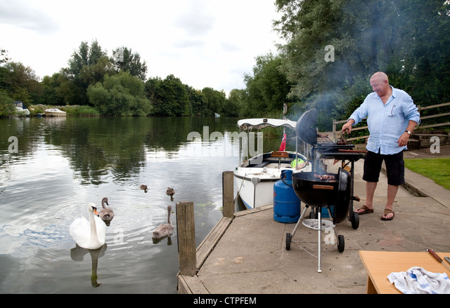Man doing a barbecue bbq on the river bank, the River Thames at Wallingford Oxfordshire UK - Stock Image