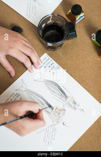 Young womans hands painting fashion design on work table - Stock Image
