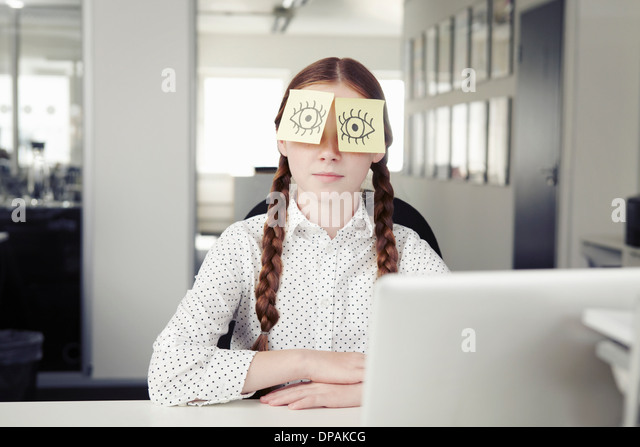 Girl in office with adhesive notes covering eyes - Stock Image