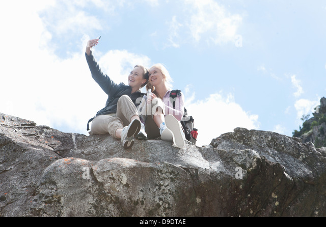 Two girl hikers taking self portrait on top of rock formation - Stock Image