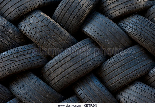 Car tyres stacked up at garage - Stock Image