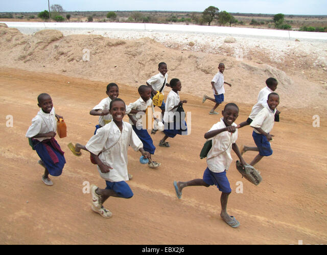 children in school uniforms running on unpaved road with a smile near the administrative capital, Tanzania, Dodoma, - Stock Image