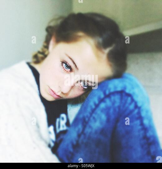 Girl with French plait looking sad thoughtful. - Stock Image