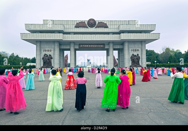 Women in colourful traditional dresses at mass dancing, Pyongyang, North Korea - Stock Image