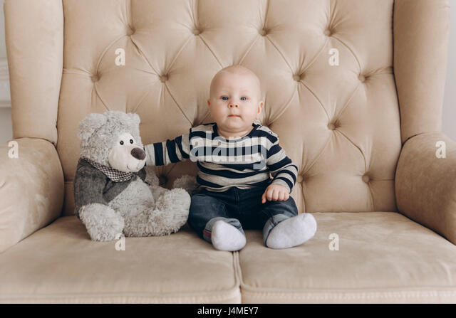 Portrait of Caucasian baby boy sitting on love seat with teddy bear - Stock-Bilder