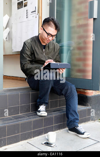 Male architect using digital tablet on office step - Stock Image