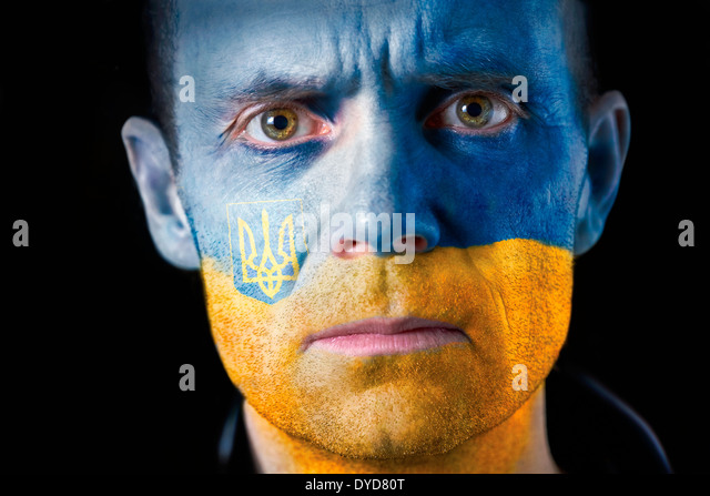 An intense stare from a man with their face painted with the Ukrainian flag. - Stock Image
