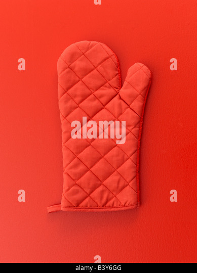 Red oven mitt on red background - Stock Image