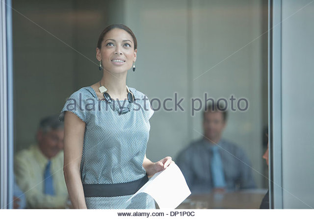 Smiling business woman holding a paper and looking up - Stock Image