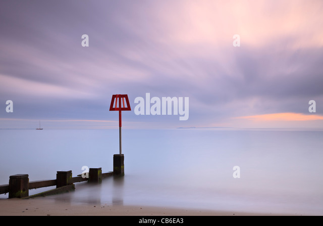Groyne marker, Swanage Bay, Dorset, UK, at dawn - Stock Image