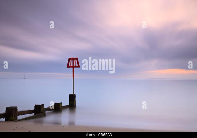 Groyne marker, Swanage Bay, Dorset, UK, at dawn - Stock-Bilder