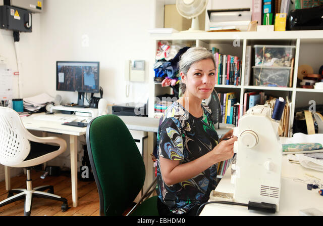 Designer working at sewing machine in studio - Stock Image