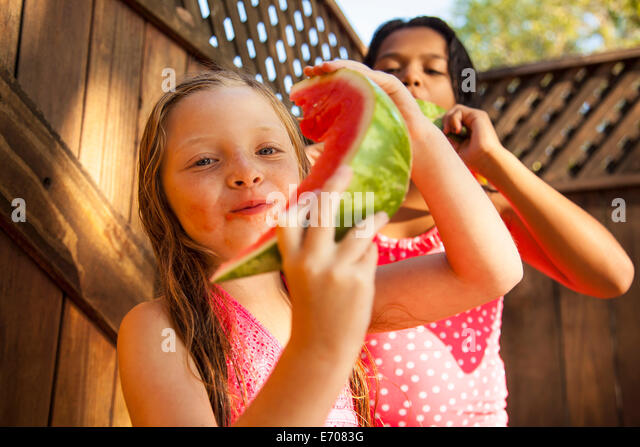 Two girls eating slices of watermelon in garden - Stock Image