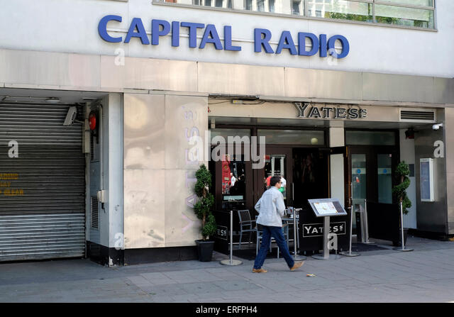 A woman walks past Capital radio station in Leicester Square - Stock Image