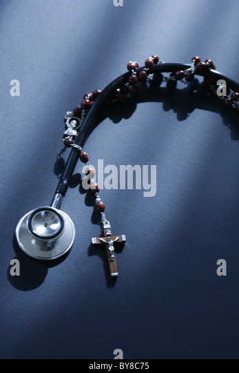 a stethoscope and a rosary entwined modern medical science versus religion - Stock Image
