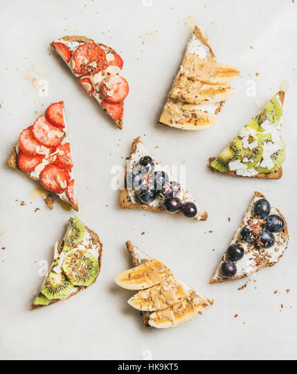 Healthy breakfast toasts cut in pieces. Wholegrain bread slices with cream cheese, various fruit, seeds and nuts. - Stock Image
